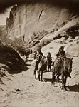 Band of mounted Navahos passing through Canon
