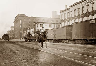 Boy on horse, railroad cars 11th Ave New York City