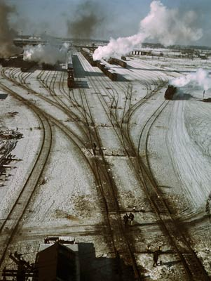 Steam rising from trains in snow covered tracks
